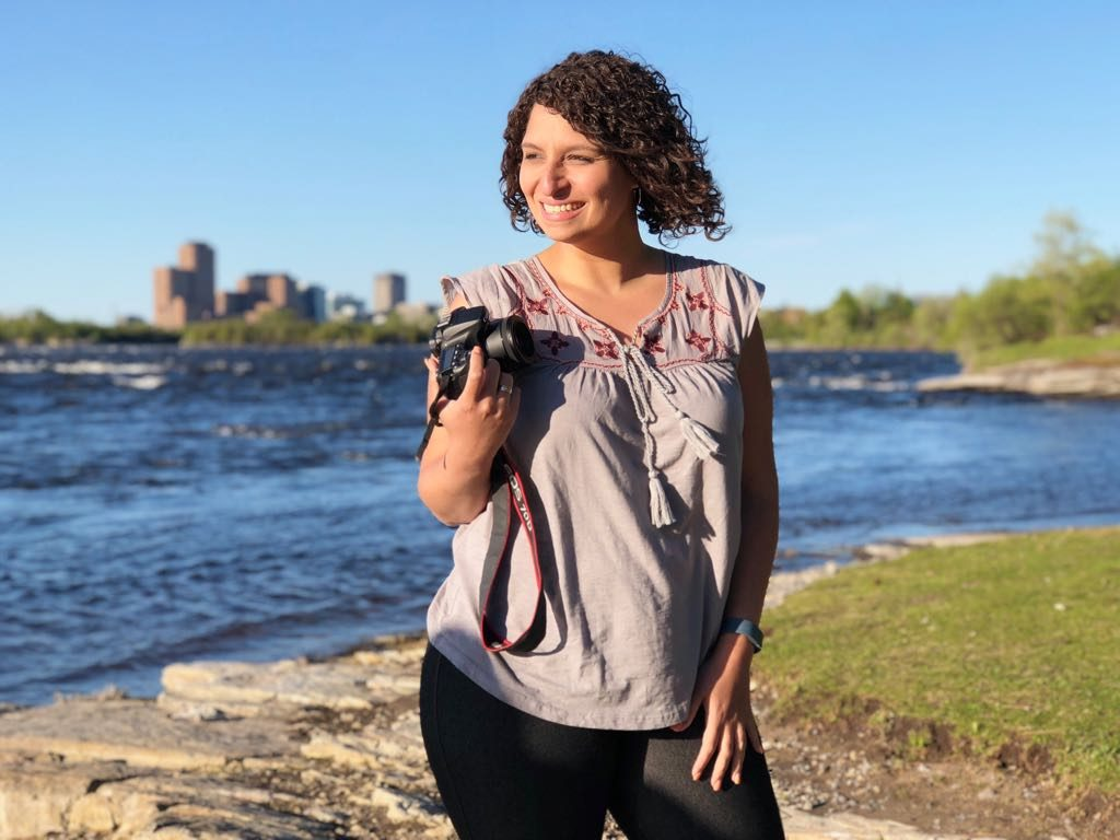 Ambar Gordon, photographer in Burlington, posing in front of a river with a professional camera on her right hand